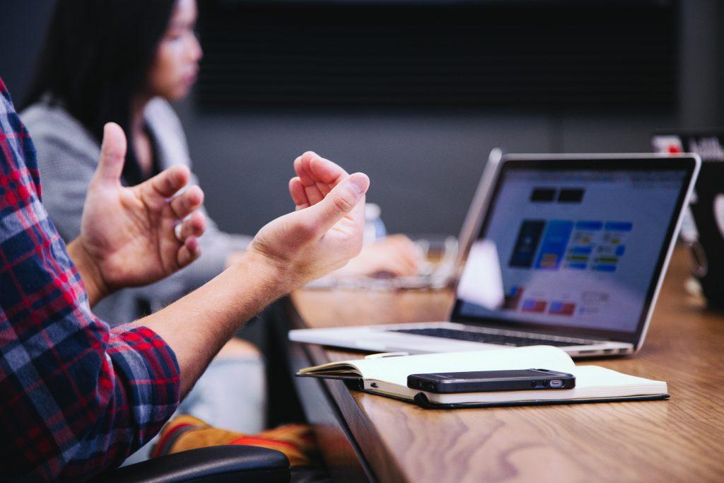 Persona masculina viendo una computadora y explicando a otra persona femenina.