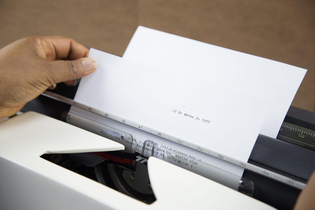 Una mano sosteniendo una hoja blanca que se encuentra dentro de una máquina de escribir.
